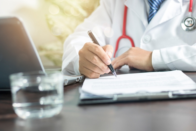 doctor writing information to patient on medicine paper in clini