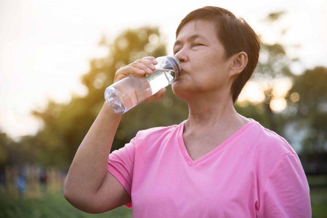Asian senior Female drinking water.